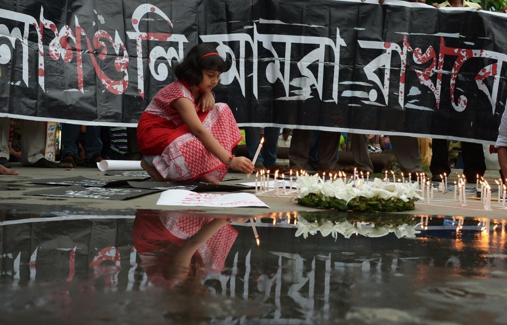 Una bambina accende una candela durante una manifestazione di condanna all'attentato jihadista di Dhaka, che si è tenuta a Calcutta, in India, il 2 luglio 2016. Nell'attacco, rivendicato dal gruppo Stato islamico, sono rimaste uccise venti persone, tra cui anche una ragazza indiana di 19 anni. - Dibyangshu Sarkar, Afp